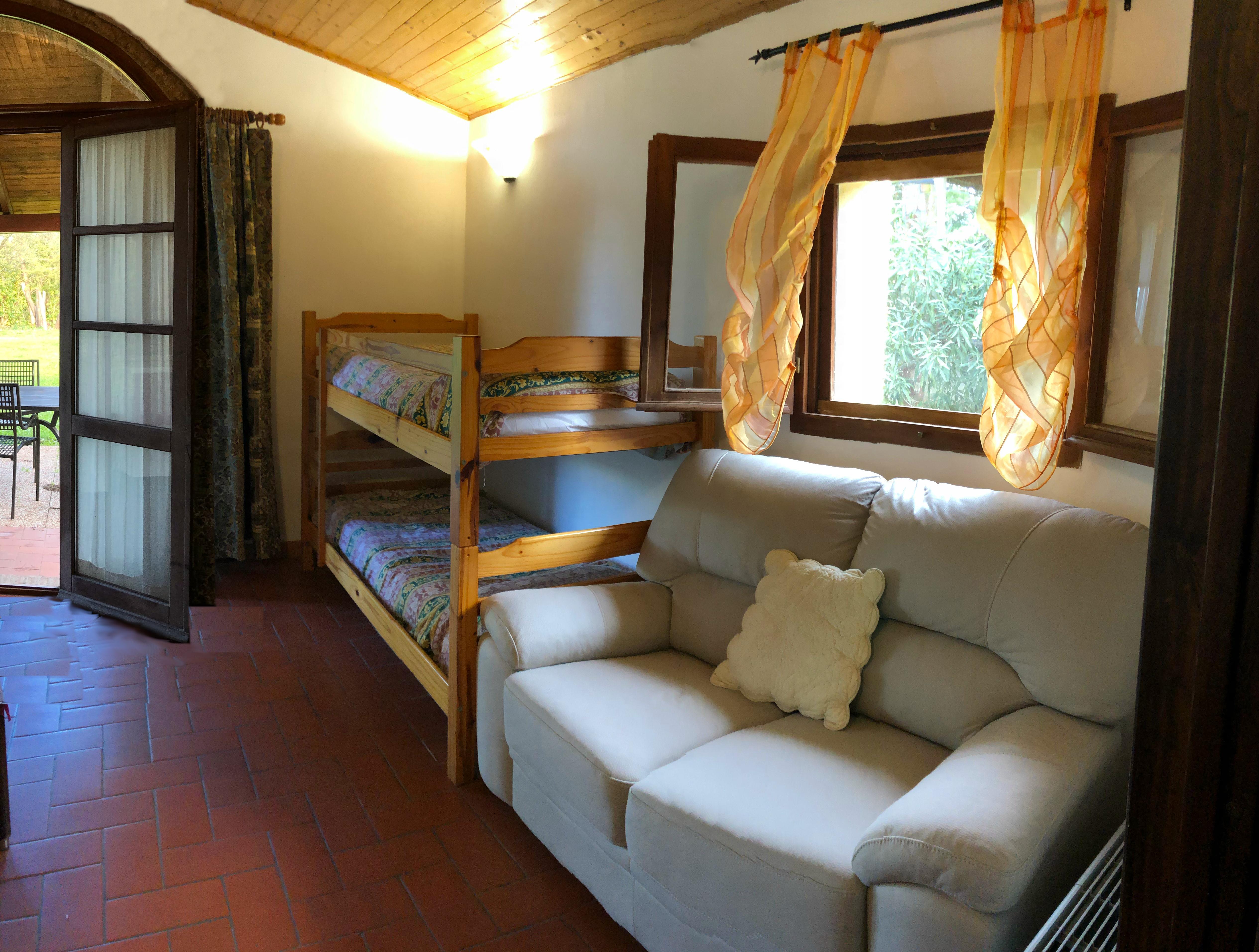 Appartamento Rondine: dettaglio del soggiorno con divano, letto a castello, finestra e porta aperta con vista sul giardino